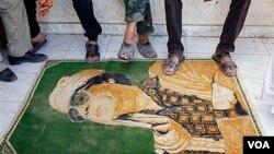 Los rebeldes libios usan de alfombra una imágen de Moammar Gadhafi, a la entrada del campamento en Tarhouna.