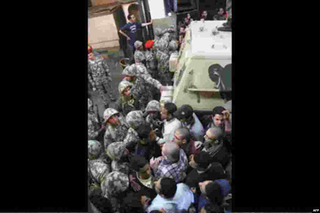 Egyptian soldiers, left, are unsuccessful as they try to stop angry protesters who storm the state security building headquarters in Cairo's northern Nasr City neighborhood, Egypt, Saturday, March 5, 2011.