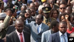 Le président zimbabwéen Robert Mugabe, au centre, salue de la main après s'être adressé aux membres de l'Association des anciens combattants de la guerre de libération nationale du Zimbabwe, au siège du parti, Harare, 27 juillet 2016.