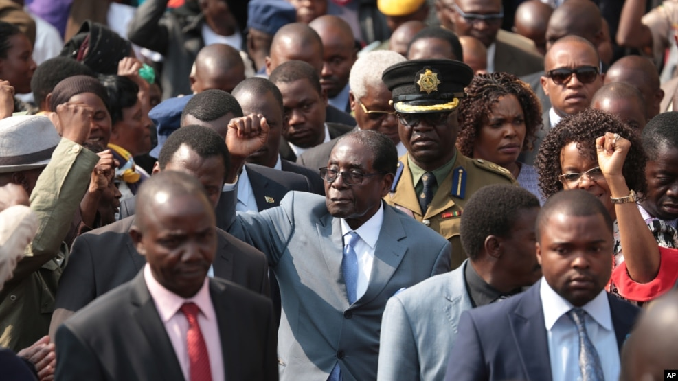 Zimbabwean President Robert Mugabe, centre, gestures after addressing members of the Zimbabwe National Liberation War Veterans Association, at the party headquarters, in Harare on July, 27, 2016.