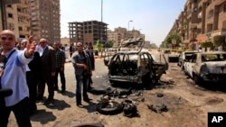 Petugas keamanan Mesir memeriksa sebuah mobil yang hancur akibat ledakan bom di Kairo, Kamis (5/9).