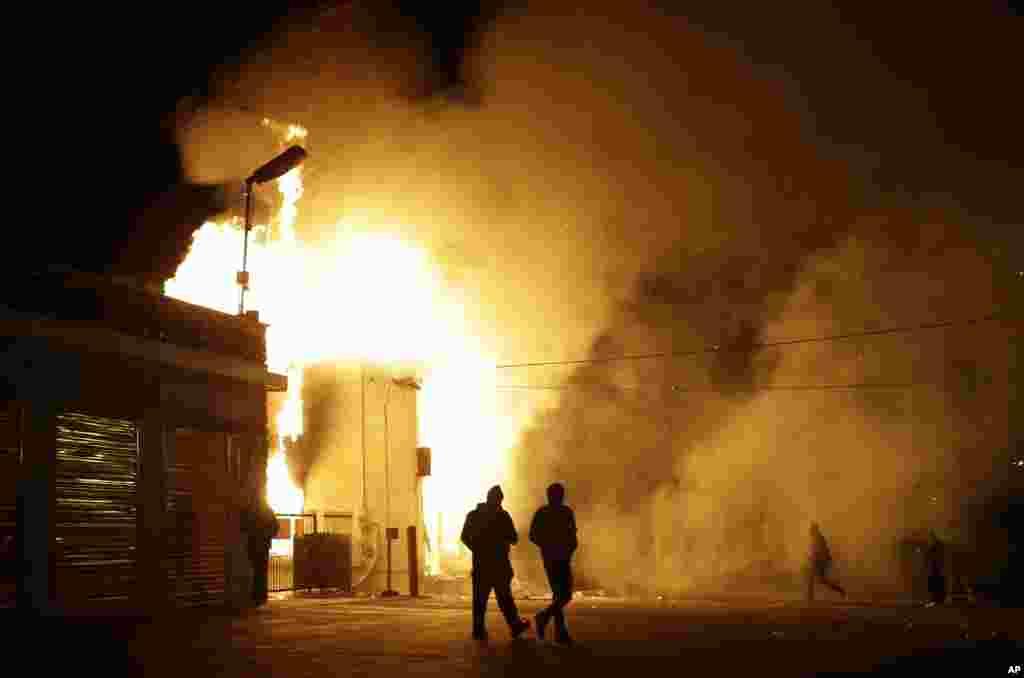 Warga menjauhi gudang yang terbakar menyusul kerusuhan setelah pengumuman dewan juri pengadilan Missouri, Senin (24/11) di Ferguson, Missouri.(AP/Jeff Roberson)