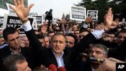 Ông Ekrem Dumanli, tổng biên tập nhật báo Zaman chào các ủng hộ viên đang reo hò, khi ông bị câu lưu bên ngoài văn phòng của ông ở Istanbul, Thổ Nhĩ Kỳ, 14/12/14