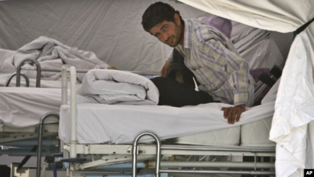 A Syrian refugee waits for medical assistance on a bed in a field hospital set up by the Turkish Health Ministry in a camp in Yayladagi ,Turkey, near the Syrian border, Sunday, June 12, 2011.