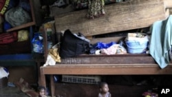 Ivorian toddlers Prencia Gosse, left, and Laure Djiejian, who along with their families fled ethnic and political clashes, play alongside piled belongings in a classroom at the Catholic Mission in Duekoue, in western Ivory Coast (File Photo - May 30, 2011
