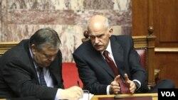 Menteri Keuangan Yunani Evangelos Venizelos (kiri) dan PM George Papandreou saat memberikan keterangan di depan parlemen Yunani di Athena (30/6).