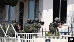 Polisi San Diego Police bersiap memasuki rumah tersangka penembakan di kota itu (29/7). (AP/Denis Poroy)