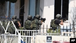San Diego Police SWAT officers prepare to enter house with a possible suspect inside in San Diego, July 29, 2016.