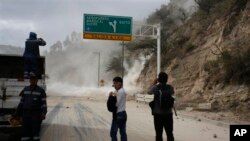 People watch as earth, dust spill on the Pan-American highway as result of an earthquake, north of Quito, Ecuador, Aug. 12, 2014.