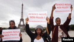 """Women hold placards which read, """"Bring back our girls"""", during a demonstration near the Eiffel Tower in Paris, May 13, 2014."""