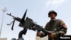 Seorang anggota pasukan keamanan Afghanistan berjaga-jaga di dalam kendaraan tentara di pangkalan udara AS Bagram, setelah pasukan Amerika mengosongkannya, di Provinsi Parwan, Afghanistan, 5 Juli 2021. (Phoro: REUTERS/Mohammad Ismail)