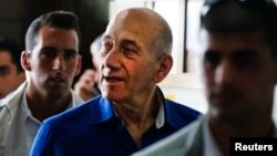 FILE - Former Israeli Prime Minister Ehud Olmert (center) leaves Tel Aviv District Court, May 13, 2014. Olmert was sentenced to six years in jail on Tuesday for taking bribes in a massive real estate deal.