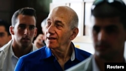 FILE - Former Israeli Prime Minister Ehud Olmert (C) leaves Tel Aviv District Court.
