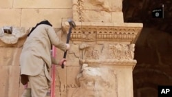 FILE - This image from a video posted on a website frequently used by Islamic State shows a militant hammering at a face on a wall in Iraq's ancient city of Hatra, April 3, 2015.