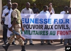 A soldier walks past Malians protesting the junta's arrest of several prominent figures, in front of the hotel where interim president Dioncounda Traore is staying. The sign reads in part, 'Military to the front lines, power to civilians'. Bamako, April 1