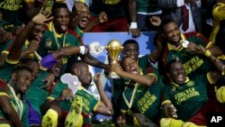 Cameroon players celebrate with the trophy after winning the African Cup of Nations final soccer match between Egypt and Cameroon at the Stade de l'Amitie, in Libreville, Gabon, Sunday, Feb. 5, 2017. Cameroon won 2-1