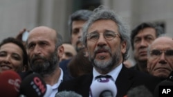 FILE - Can Dundar, the editor-in-chief of opposition newspaper Cumhuriyet, right, and Erdem Gul, left, the paper's Ankara representative, speak to the media after the opening of their trial in Istanbul, March 25, 2016.