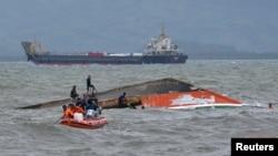 Lực lượng cứu hộ buộc dây thừng vào chiếc phà bị lật MBCA Kim-Nirvana để kéo vào bờ gần 1 cảng ở thành phố Ormoc, miền trung Philippines, 3/7/2015.