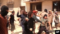In this picture posted on a social media account affiliated with the Islamic State group, June 14, 2015, IS militants stone a man accused of violating the extremists' ban on homosexuality after they threw him from a roof in the city of Homs, Syria.