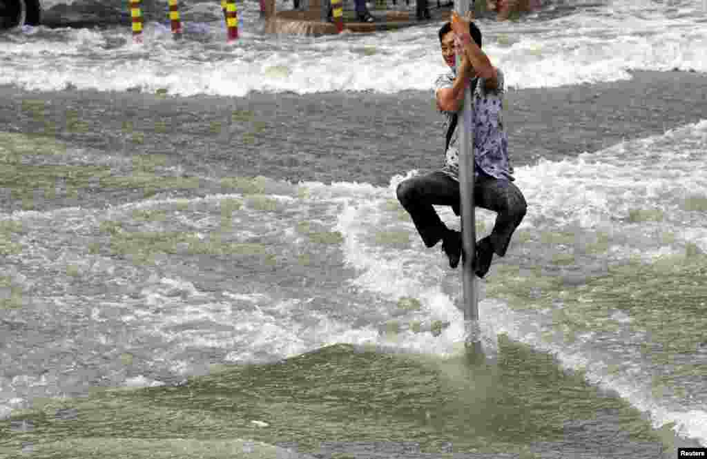 A man climbs on a road sign pole to escape the water from a tidal bore which surged past a barrier on the banks of Qiantang River, in Hangzhou, Zhejiang province, China, Sept. 1, 2015.