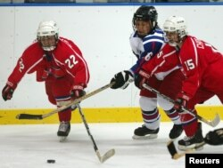 FILE - A South Korean player (white jersey) struggles for the puck during a women's ice hockey match at the fifth Winter Asian Games in Misawa, Japan, Feb. 3, 2003. Seoul has proposed a joint North-South Korean women's hockey team for the Pyeongchang Olympics next month.