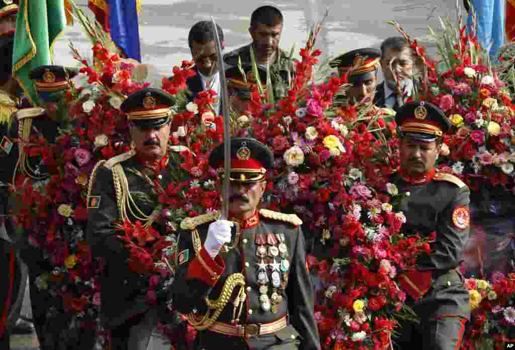 Afghan guards of honor carry wreaths during a ceremony commemorating the 12th anniversary of Ahmad Shah Massoud's death in Kabul.