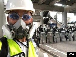 美國之音記者在香港機場報導香港反中民眾機場示威防暴警察清場的實況。(美國之音記者黎堡拍攝)