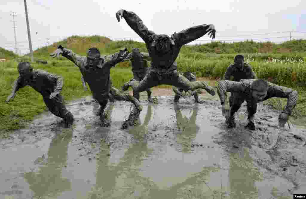 Paramilitary policemen jump during a training session in muddy water at a military base in Chuzhou, Anhui province, China.