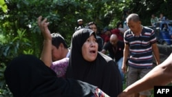 FILE - A woman calls out to her relatives after identifying bodies dumped off a cliff along the highway leading to Marawi on the southern island of Mindanao on May 28, 2017.