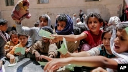 FILE - Yemenis present documents in order to receive food rations provided by a local charity, in Sana'a, Yemen, April, 13, 2017.