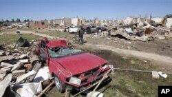 Calvin Smith of Tuscaloosa, Alabama, pushes his bike past tornado demolished homes in Tuscaloosa, Alabama, April 29, 2011