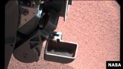Kendaraan penjelajah Mars, Curiosity mengambil tanah sample dari planet Mars (Foto: dok). Para ilmuwan tengah berupaya memecahkan misteri bintik purih yang muncul dari tanah mars dari hasil penggalian ini.