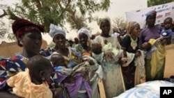 Women wait to receive baby food in the village of Koleram, southern Niger, during the launch of a UN-backed blanket feeding operation aimed at fighting malnutrition among children under the age of two, 28 Apr 2010