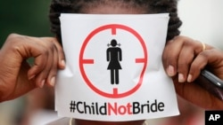 FILE - A woman protests against underage marriages in Lagos, Nigeria, July 20, 2013. The African Union is to convene a summit in Zambia this week with a view to ending child marriage.