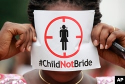 FILE - A woman protests against underage marriages in Lagos, Nigeria, July 20, 2013.