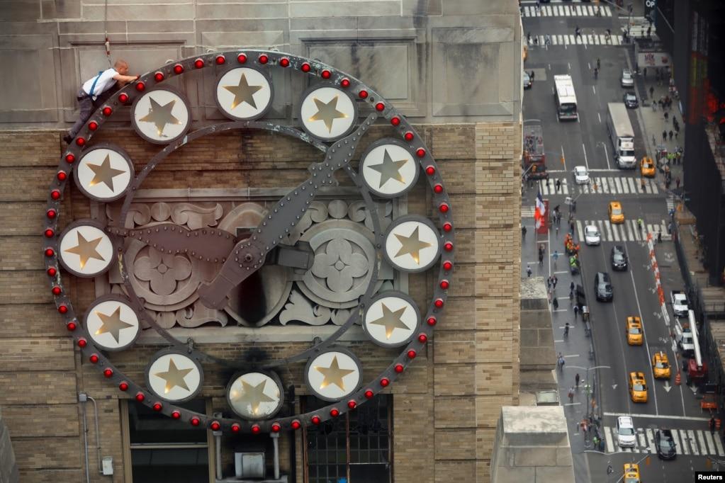 Работник заменяет несколько лампочек круглосуточно над Таймс-сквер на Paramount building в Нью-Йорке.