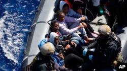 Des migrants secourus et embarqués dans un canot gonflable lors de l'opération Sophia, au large de la côte libyenne, en Méditerranée, 29 mars 2016.