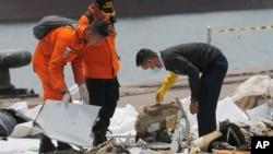 Một điều tra viên (phải) xem xét các mảnh vỡ của máy bay thuộc hãng Lion Air bị rơi hôm 13/10/2018