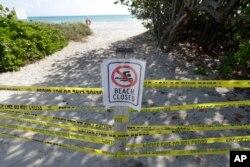 Pengumuman dilarang masuk tampan di pantai Surfside, Florida, Sabtu, 21 Maret 2020. (Foto: AP)