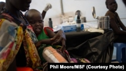 A boy who suffered severe burns to his leg is tended to by a Médecins Sans Frontières (MSF) doctor at the United Nations Mission to South Sudan base in Juba, South Sudan, Jan. 12, 2014.