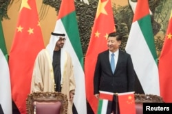 Sheikh Mohammed bin Zayed al-Nahyan (L), Crown Prince of Abu Dhabi and UAE's deputy commander-in-chief of the armed forces meets Chinese President Xi Jinping (R) during a signing ceremony at the Great Hall of the People in Beijing, Dec. 14, 2015.