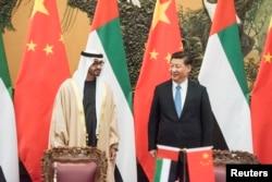 ທ່ານ Sheikh Mohammed bin Zayed al-Nahyan (ຊ້າຍ), ອົງມົງກຸດຣາຊກຸມມານແຫ່ງ Abu Dhabi ແລະ ຮອງຜູ້ບັນຊາການສູງສຸດ ຂອງກອງທັບ UAE ພົບປະກັບປະທານປະເທດຈີນ Xi Jinping (ຂວາ) ໃນຂະນະທີ່ທຳການລົງນາມໃນພິທີ ທີ່ສາລາປະຊາຊົນໃນນະຄອນປັກກິ່ງ, 14 ທັນວາ, 2015.