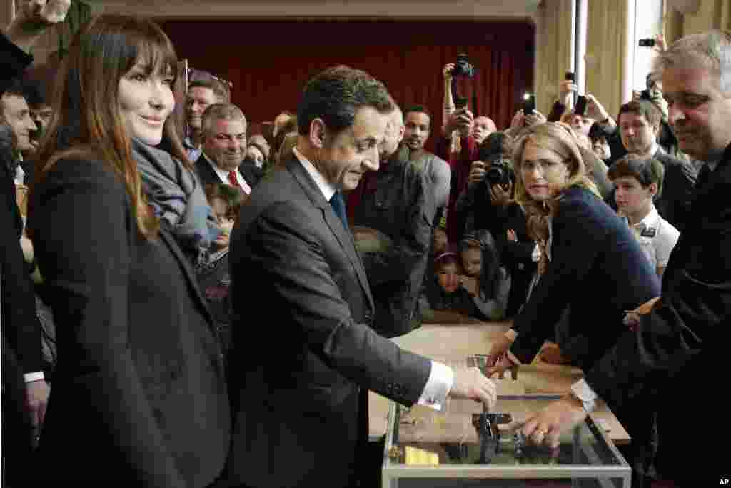 French President and UMP candidate Nicolas Sarkozy, center left, casts his vote for the second round of the presidential elections as his wife Carla Bruni-Sarkozy, left, looks on in Paris, May 6, 2012. (AP)