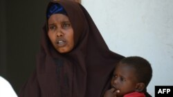 Lul Ali Osman, who claimed she was raped by security forces, is seen holding her child at the court house in Mogadishu March 3, 2013.