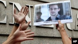 A supporter holds a picture of Edward Snowden, a former CIA employee who leaked top secret information about U.S. surveillance programs, outside the U.S. Consulate General in Hong Kong Thursday, June 13, 2013.