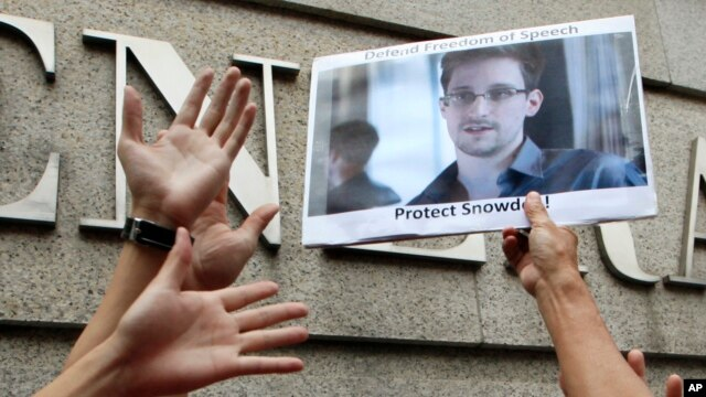 FILE - A supporter holds a picture of Edward Snowden, a former CIA employee who leaked top-secret information about U.S. surveillance programs, outside the U.S. Consulate General in Hong Kong, June 13, 2013.