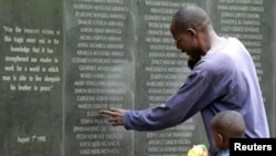 A survivor pays homage at a memorial wall listing the names of the those killed in the 1998 bombing of the U.S. Embassy in Nairobi. (Reuters)
