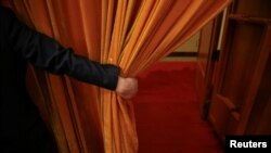 FILE - A security agent opens a curtain covering the entrance of a main hall inside the Great Hall of the People where sessions of the National People's Congress and the Chinese People's Political Consultative Conference take place, in Beijing, China, March 6, 2016.