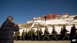 一名藏人女子在布達拉宮前拜佛時一隊中國軍人走過