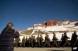 Một người phụ nữ Tây Tạng cầu nguyện trong lúc một nhóm binh lính Trung Quốc diễu hành ở phía trước Cung điện Potala ở Lhasa.